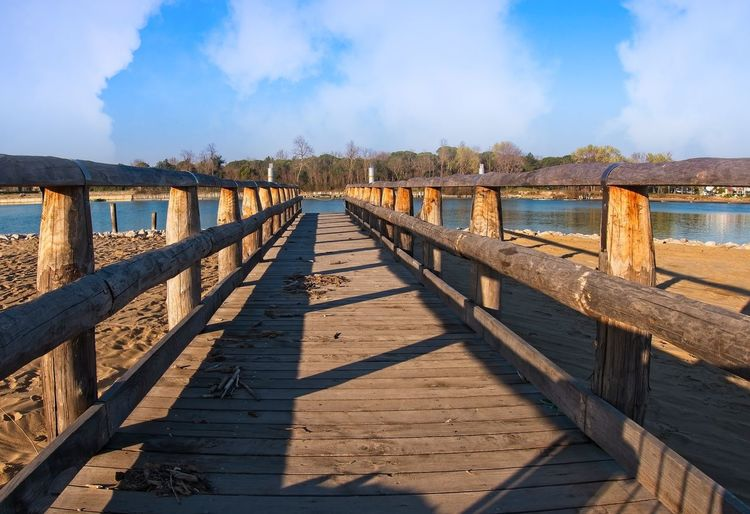 Wooden pier on the beach Water Wood - Material Sky Built Structure Nature Connection Railing Bridge Cloud - Sky Architecture No People Shadow Sunlight Day Tranquility Direction The Way Forward Tranquil Scene Sea Bridge - Man Made Structure Outdoors Wood Paneling Long Pier
