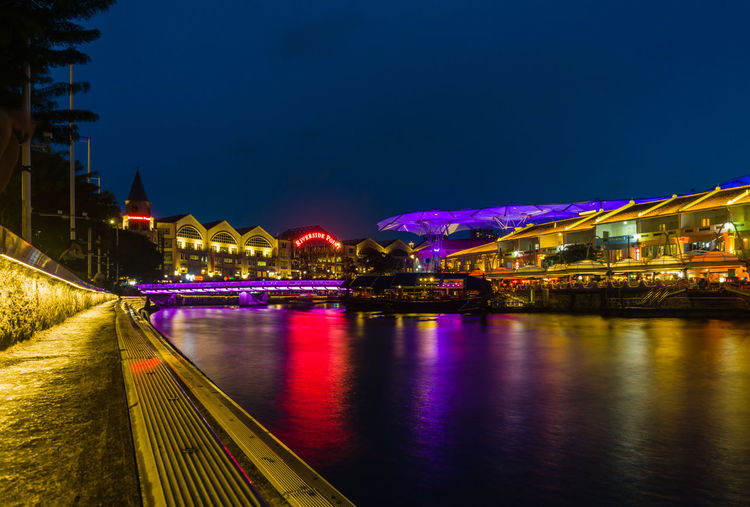 Illuminated bridge over river by buildings against sky at night