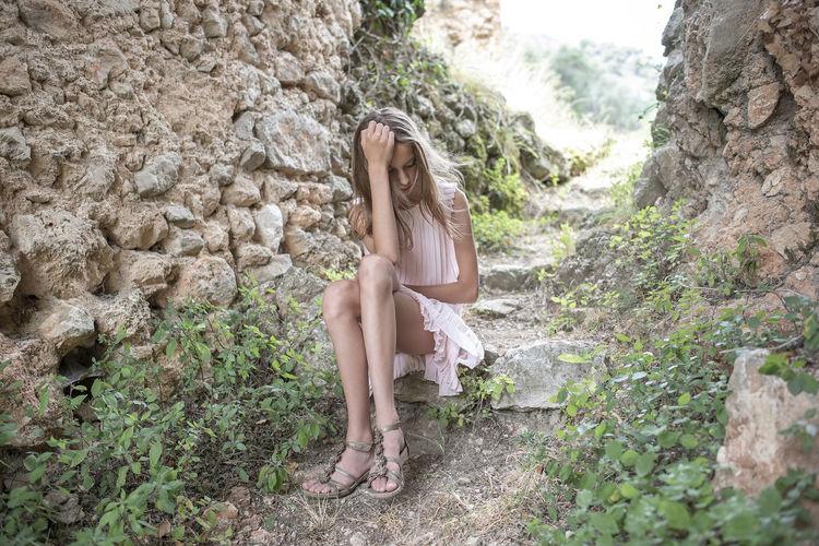 Full length of girl sitting on rock in forest