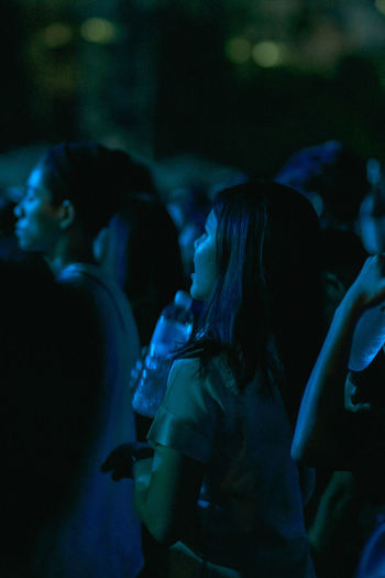 Side view of people enjoying at music concert