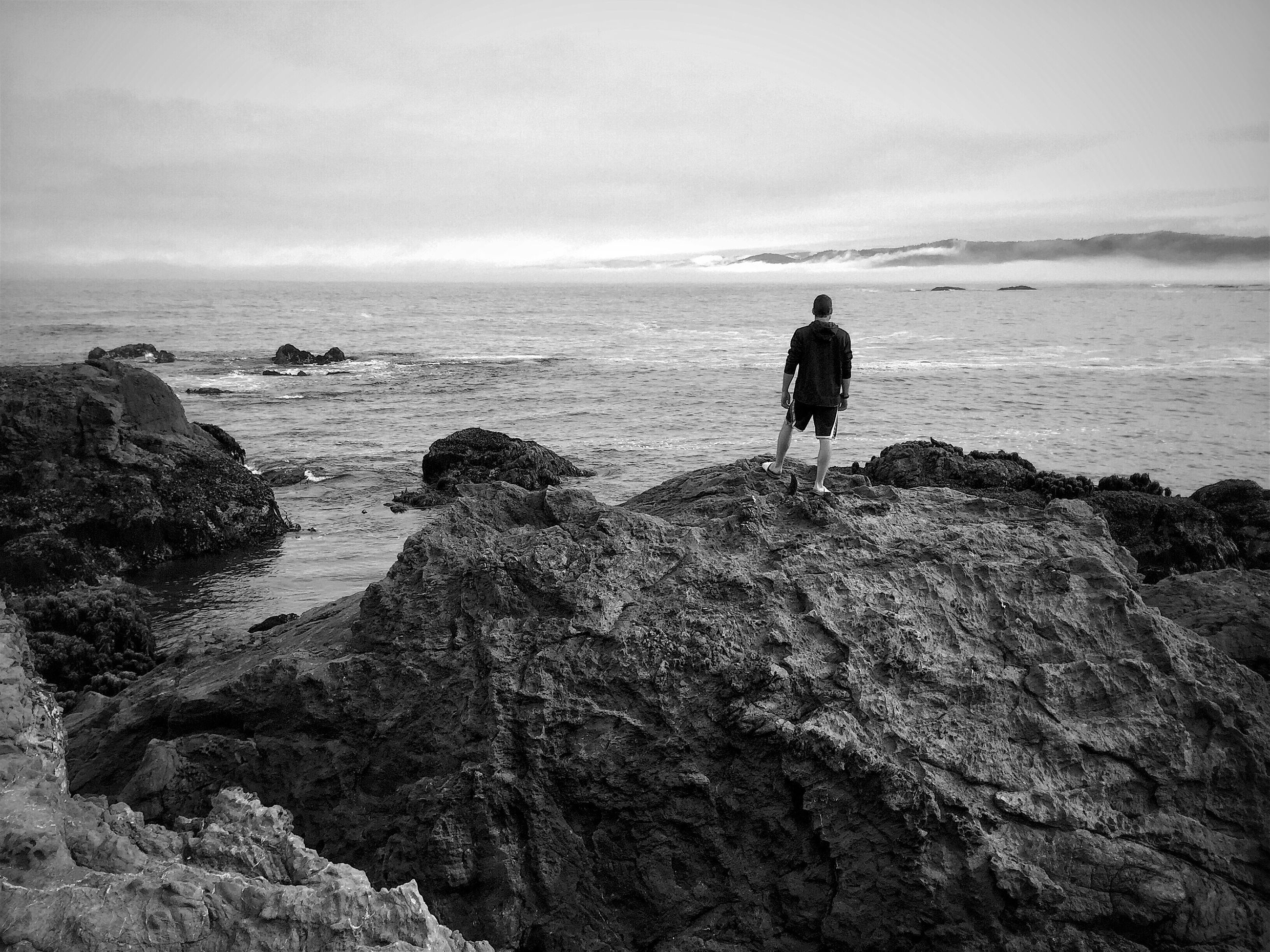 sea, horizon over water, lifestyles, leisure activity, water, full length, sky, standing, tranquil scene, tranquility, scenics, beauty in nature, nature, rock - object, shore, idyllic, vacations, remote, outdoors, cloud - sky, rock formation, day, non-urban scene, rock