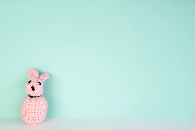 stuffed bunny toy in front of an colored background, with space next to it Studio Shot Copy Space Mammal Animal Colored Background Indoors  Animal Themes Stuffed Toy Toy Cute Representation Blue Background Creativity Single Object Small Softness Pink Color Bunny  Easter Wallpaper Holiday Creativity