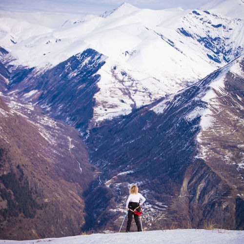 Rear View Of Woman Standing Against Snowcapped Mountains