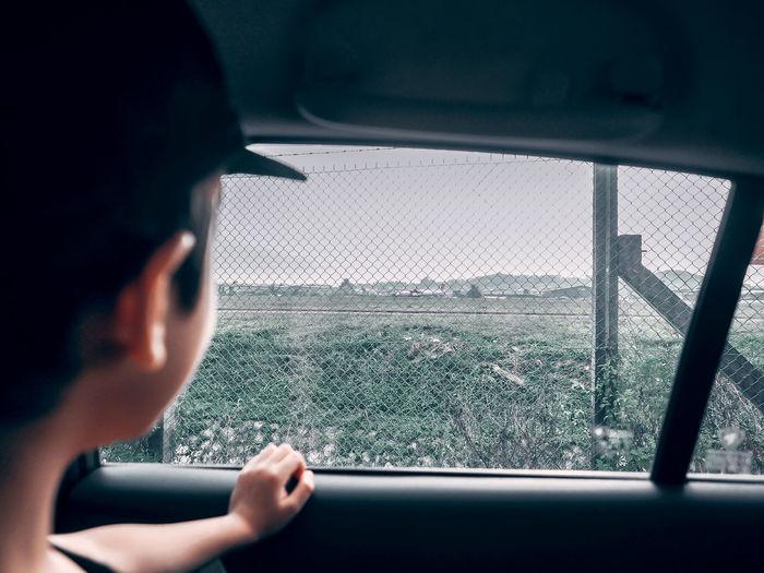 Boy looking through car window