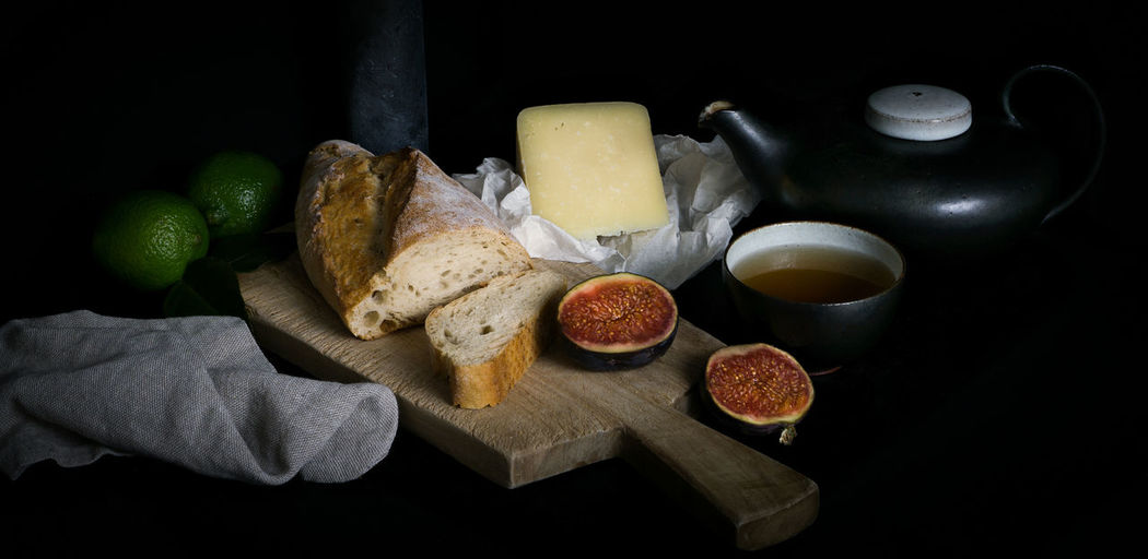 A still-life with cheese, figs and bread as a symbol for the pleasure of the simple things of life. Dark Food And Drink Light Simple Things In Life Still Life Photography StillLifePhotography Tea Bread Cheese Day Figs Food Food And Drink Fruit Indoors  Light And Shadow Lime Loaf Of Bread Moody No People Still Life Teapot Teatime Wooded Cutting Board