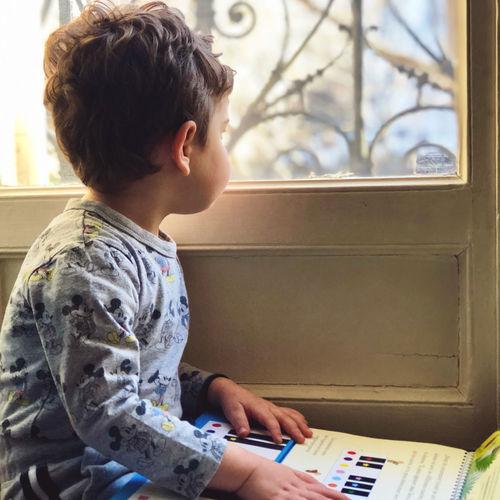 Boy looking at camera while sitting at home