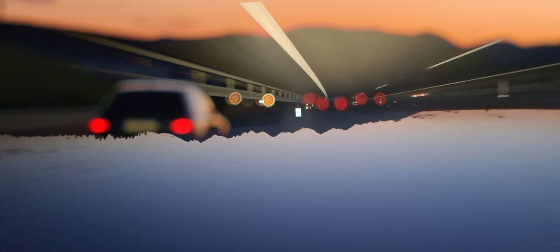 Reflection of illuminated lights on car at sunset