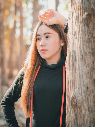 Beautiful young woman standing against tree trunk