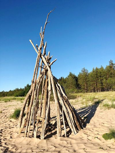 Wooden logs on field against clear blue sky