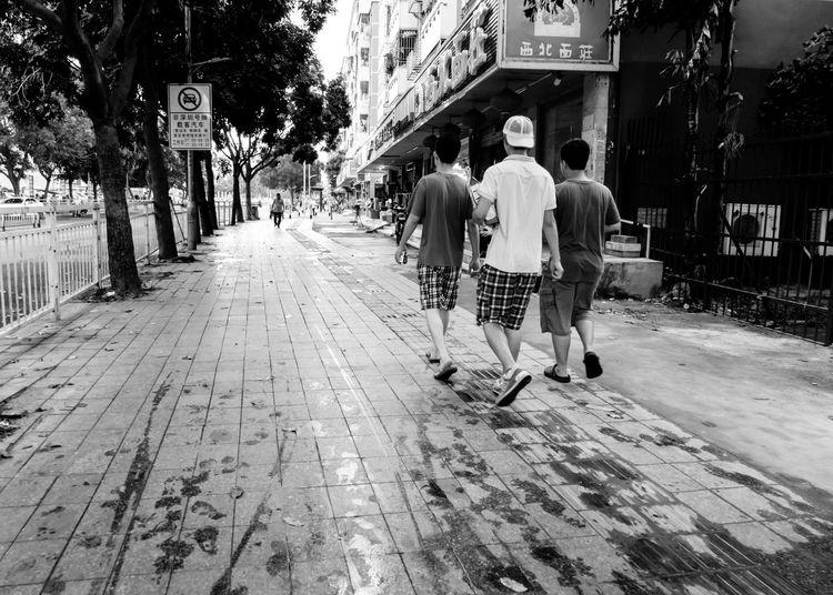 Rear view of people walking on narrow street