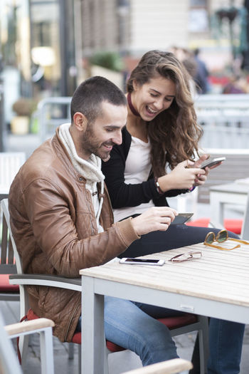 Young couple using phones