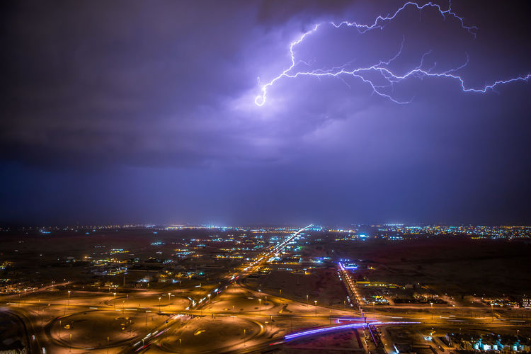 Lightning strike over illuminated cityscape
