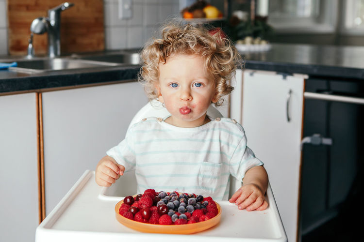 caucasian baby boy eating red fruits at home. funny child kid sitting high chair with fresh berries