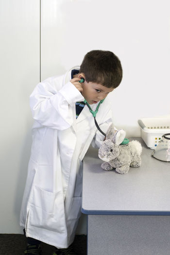 A young animal doctor pretends to listens to his bunny rabbit patient