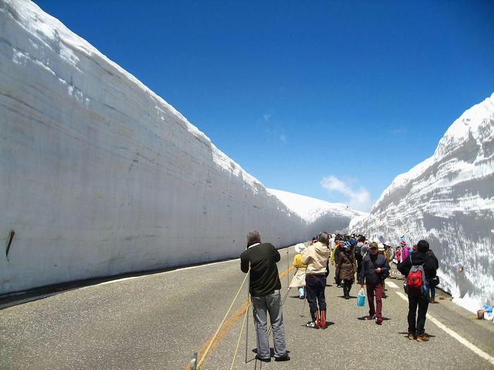 Tourists walk along snow corridor on tateyama kurobe alpine route, japanese alp in tateyama, japan.