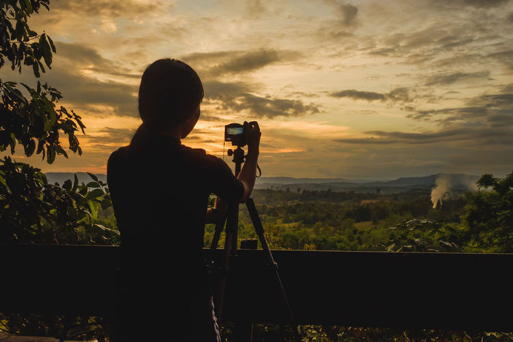 Silhouette Woman Photographing Landscape Against Sky During Sunset