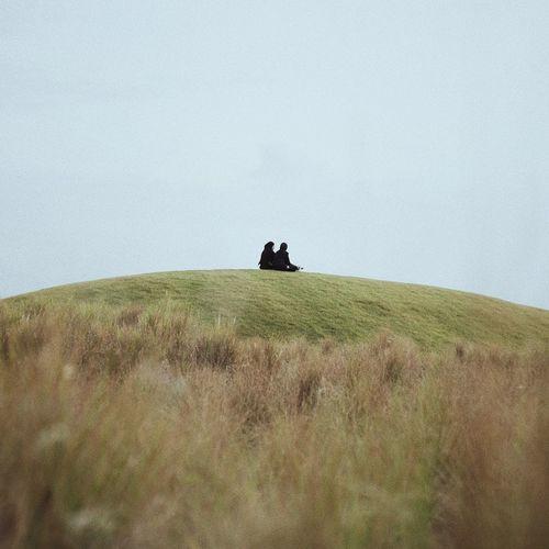 Man sitting on field against clear sky