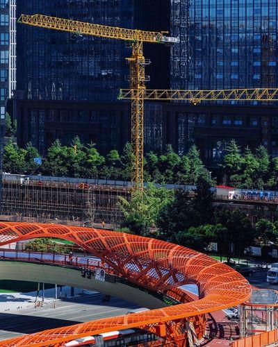 Illuminated bridge by building in city