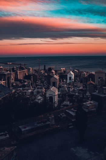 High angle view of townscape by sea against sky at sunset