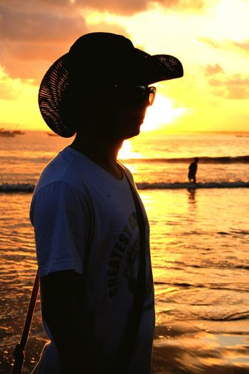 Silhouette man standing at beach against sky during sunset