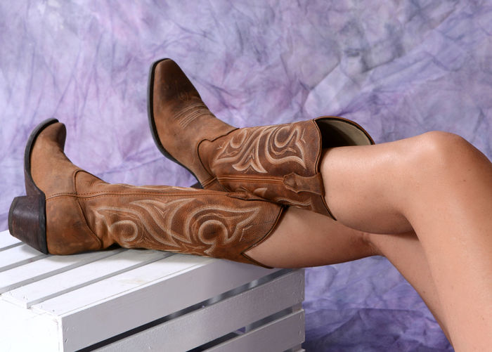 Low section of woman wearing cowboy boots against wall