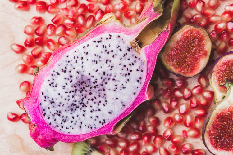 Close up sliced dragon fruit with figs and kiwi fruit, pomegranate seeds on the wooden background, top view. Flat lay. Pastel colors. Close-up Cross Section Day Food Food And Drink Freshness Fruit Healthy Eating Indoors  No People Pink Color Pitaya Pomegranate Pomegranate Seed Seed SLICE