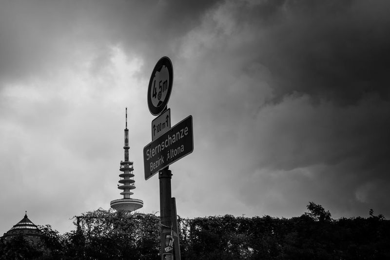 Low Angle View Of Signboard Against Cloudy Sky