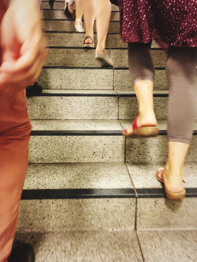 Low section of women walking on staircase