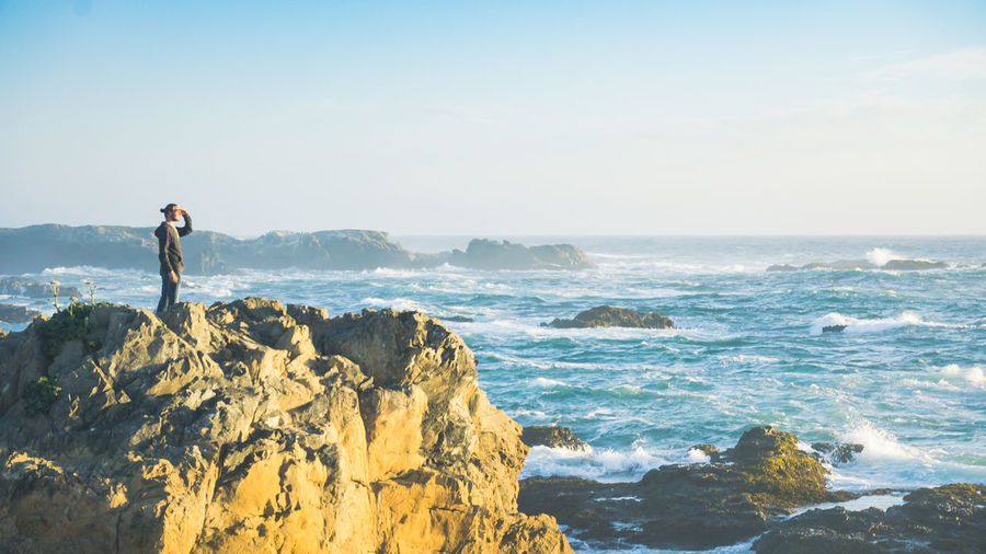 Looking at the sun rise over a rocky shoreline Sea Leisure Activity Rock Beauty In Nature Scenics - Nature Sky Rock - Object One Person Water Solid Standing Lifestyles Real People Full Length Land Nature Horizon Over Water Horizon Outdoors Looking At View Dawn Waves Crashing Waves Crashing On Rocks