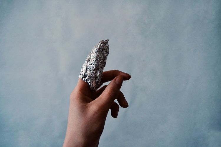 Close-up of finger wrapped in foil against sky
