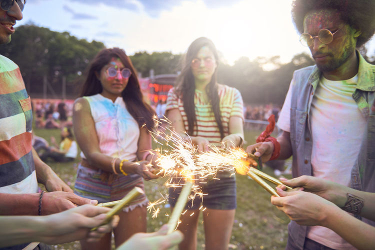 Friends holding illuminated sparklers at carnival