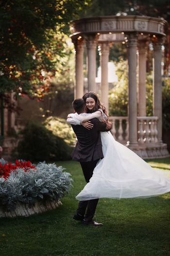 The groom circles the bride in his arms in a beautiful summer garden