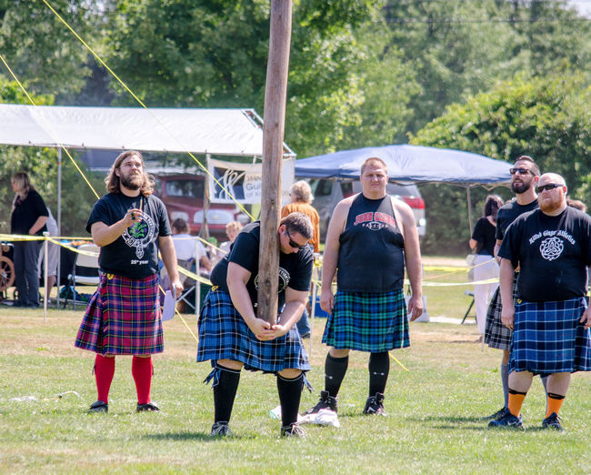 August 2017 Kalamazoo scottish festival in Michigan USA; people take part in a traditional Scottish athletic event in which competitors toss a large tapered pole called a caber Event Highland Games Scottish Scottish Festival Athletic Event Caber Toss Competition Competition Day Day Editorial  Females Full Length Group Of People Kilt Male Men People Plaids Traditional Scottish Clothing Women