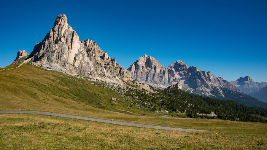 Beauty In Nature Blue Clear Sky Day Dolomites Grass Italy Landscape Mountain Mountain Peak Mountain Range Nature No People Outdoors Passo Giau Physical Geography Road Rock - Object Scenics Sky Sunlight