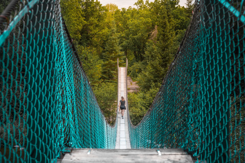 Rear view of woman walking on pinawa suspension bridge