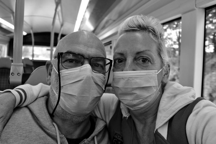 Close-up portrait of couple wearing masks in bus
