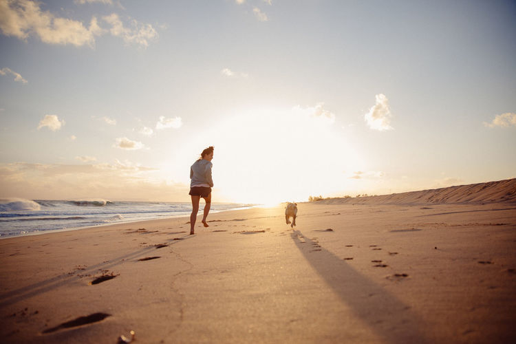 Rear view of woman with dog running at beach against sky