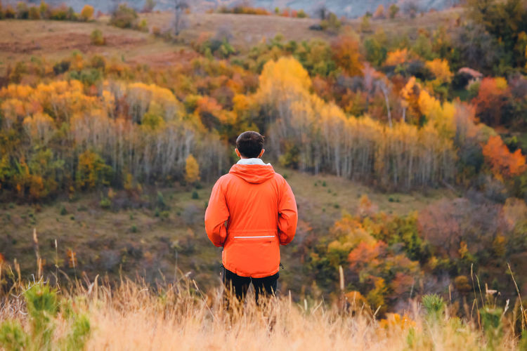 Rear view of man standing on field during autumn