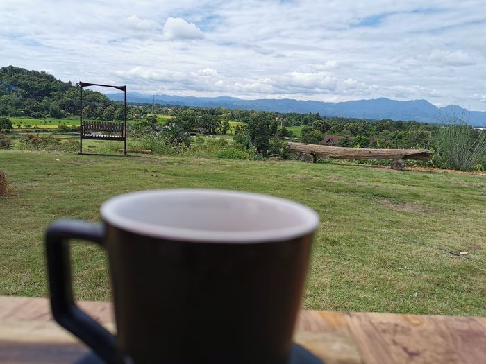 Tea cup on table by field against sky