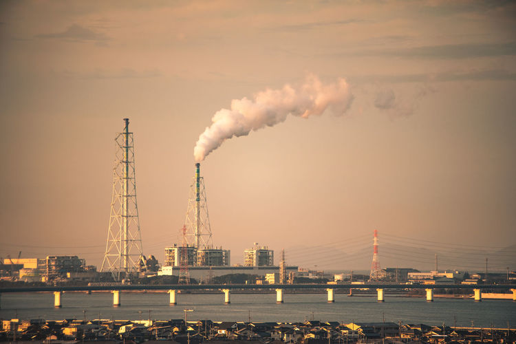 Industry Built Structure Smoke - Physical Structure Factory Building Exterior Architecture Water Pollution Smoke Stack Sky Emitting Environmental Issues River Nature Environment Tall - High Chimney City Waterfront No People Air Pollution Outdoors Fumes Atmospheric Ecosystem