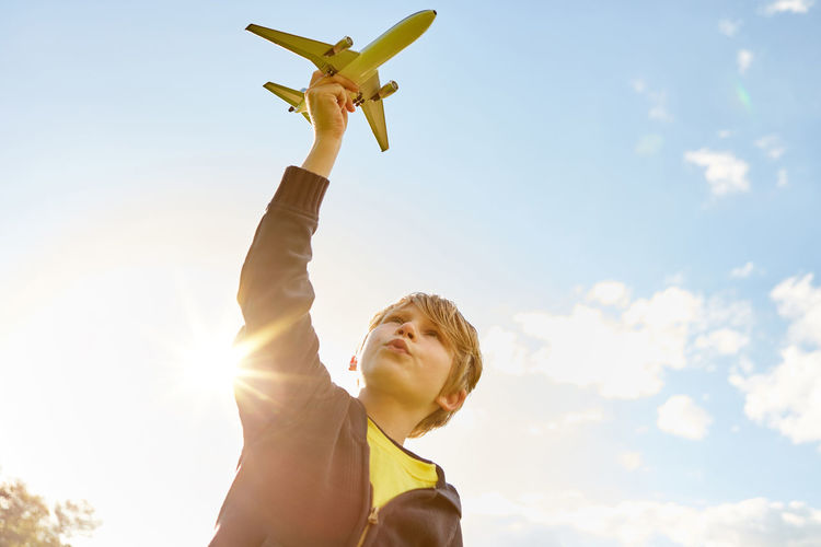 Low angle view of boy against sky on sunny day