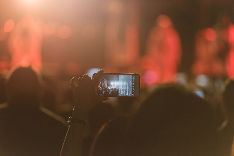 Cropped hands of woman photographing with smart phone at music concert