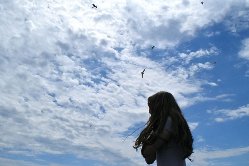People Low Angle View One Person Sky Flying Cloud - Sky Outdoors DaySeagull Nature Mid-air Spread Wings One Woman Only Bird Animal Themes Nature Only Women Mammal The Great Outdoors - 2017 EyeEm Awards Place Of Heart Connected By Travel