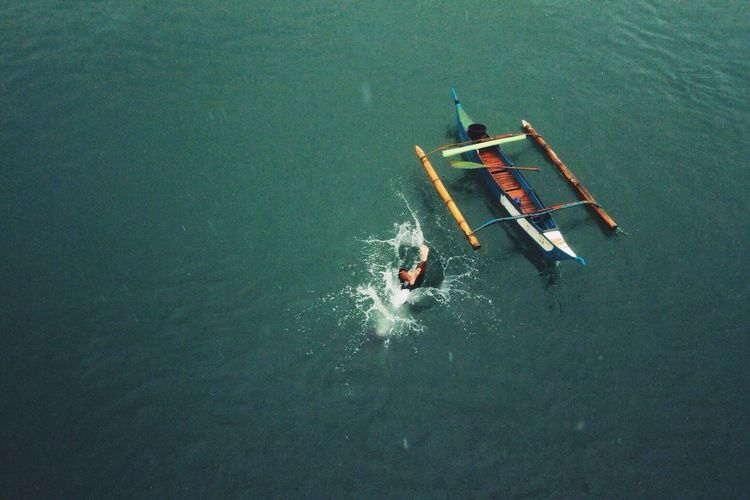 Aerial view of person diving into sea by outrigger canoe
