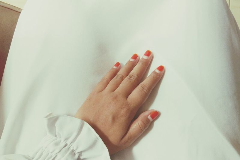 Low Section Of Woman In White Dress Wearing Red Nail Polish
