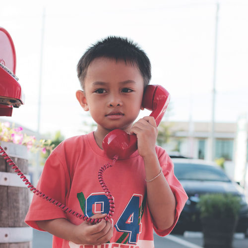 Cute boy talking on phone while standing against clear sky