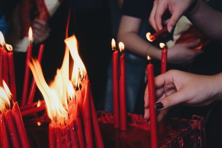 Midsection of people holding burning candles in temple