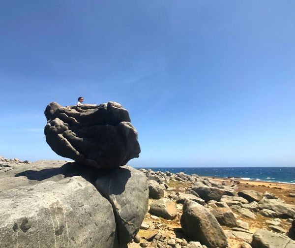 Sculpture on rock by sea against sky