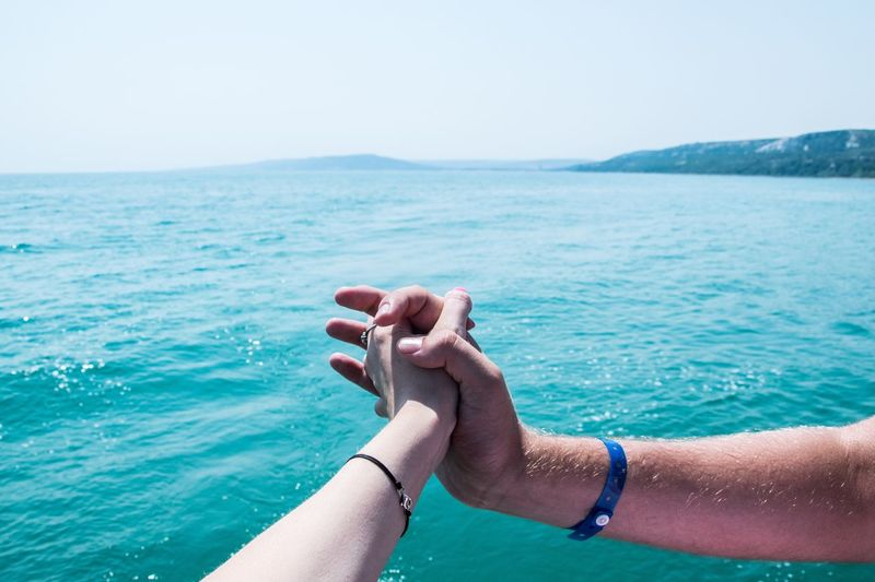 Cropped image of people holding hands against sea