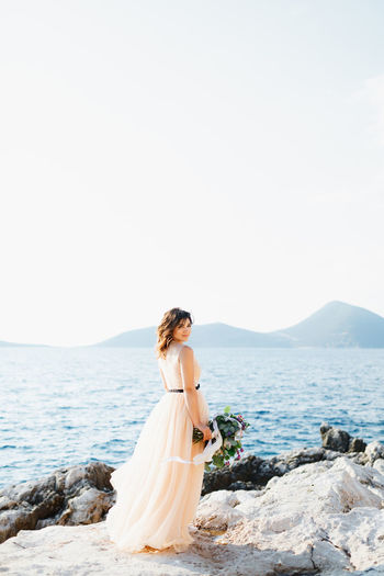 Woman standing on rock by sea against sky